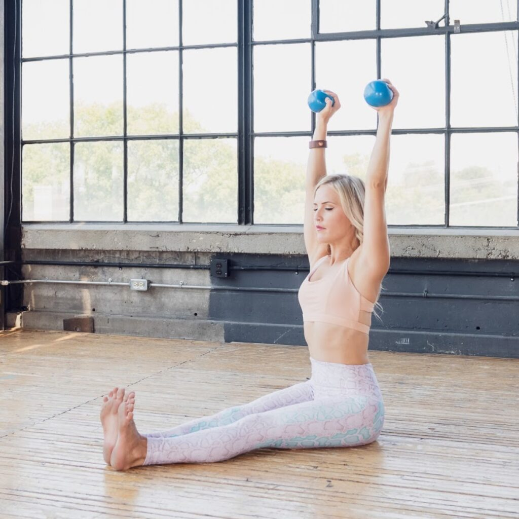 Natalya in a brightly lit pilates loft studio using a two 2lb weights with one in each hand